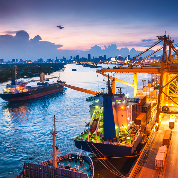A dock, with large shipping boats being loaded with marine cargo - Redwood Business Insurance Services.