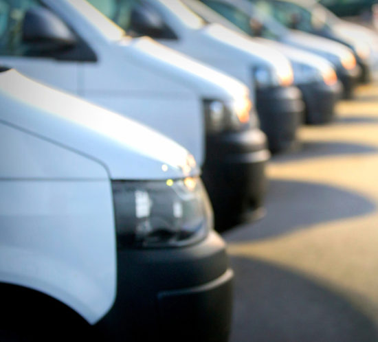 A commercial motor fleet consisting of several white vans - Redwood Business Insurance Services.
