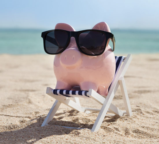 A piggy bank with sunglasses, sitting on a deckchair at the beach - Redwood Business Insurance Services.